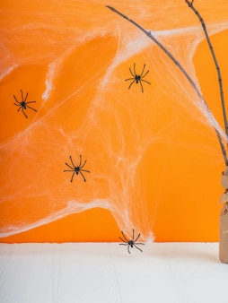 クモの巣の背景、コウモリとクモの巣、ハロウィーンとオレンジ色の背景の前に空の素朴なテーブル