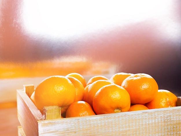 Спелые вкусные мандарины с листьями в деревянной коробке на белом