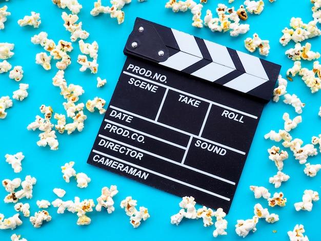 ポップコーンとカチンコ。映画、映画、エンターテイメント、広告の概念