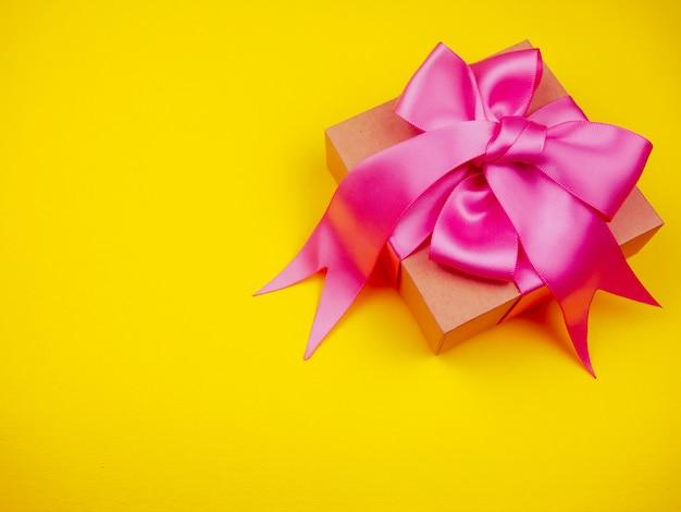 黄色の背景にピンクのサテンリボン付きギフトボックス