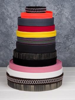 Лента разных цветов в катушках, много разноцветных катушек для текстильной промышленности, производства одежды