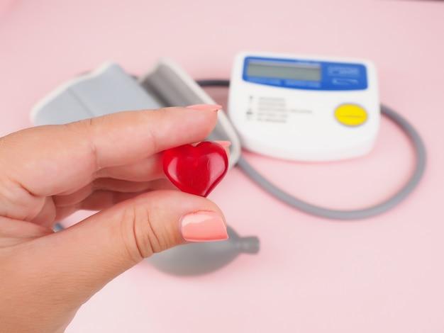 Пульсиметр на столе врача для диагностики сердечной болезни черной поверхности, манжеты для измерения артериального давления и маленького сердца в руке, тонометр, вид сверху