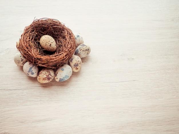 木製の背景に巣の中のウズラの卵
