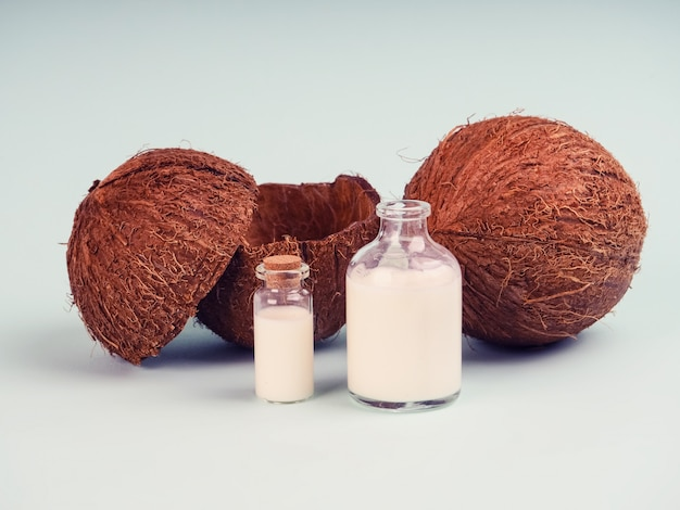 青いテーブルのココナッツとココナッツミルク。ココナッツオイルと新鮮なナッツ。ココナッツミルク、研究用試験管内の削りくず油、スーパーフード、天然油、化粧品