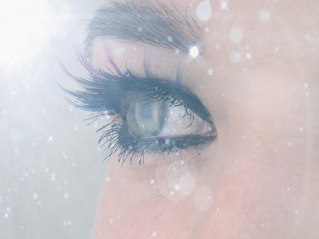光と色合いの反対側の美しい女性の目のクローズアップ、目をそらす、視力矯正の概念、しわのある自然の美しさ