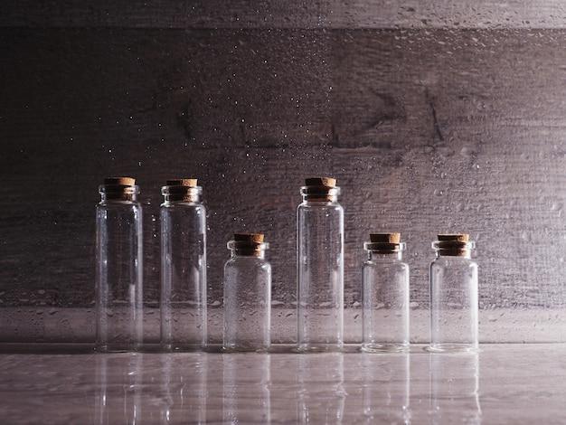 Маленькие стеклянные бутылки с пробковой крышкой. пустые пузырьки в контурном свете