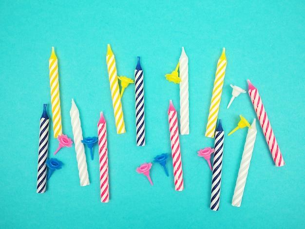 青色の背景、休日のテーマに散在しているたくさんの誕生日の蝋燭