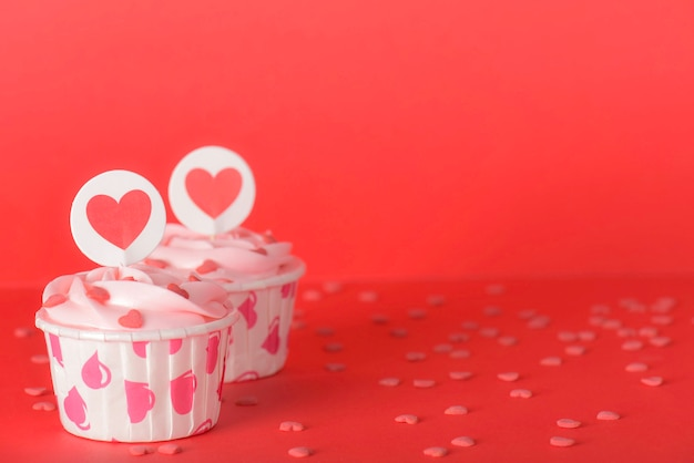 赤の背景においしいピンクパステルバタークリームカップケーキ