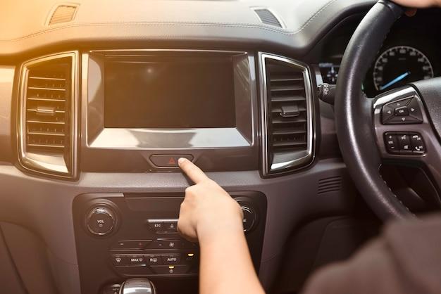 車のダッシュボードの緊急ボタンを押すと女性の指。交通機関のコンセプトです。