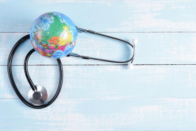 聴診器と青と白のパステル調の木製の背景に世界中。ヘルスケアと医療の概念