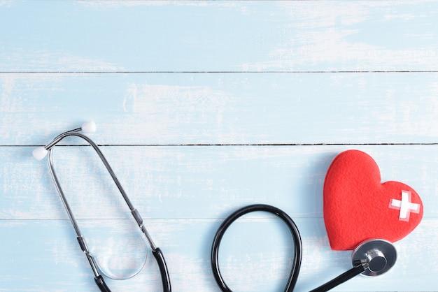 青と白のパステル調の木製の背景に聴診器で赤いハート。