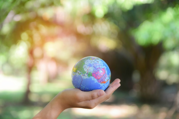 自然の緑の背景を持つ彼女の手に世界のボールを保持している女性。世界環境デーのコンセプトです。