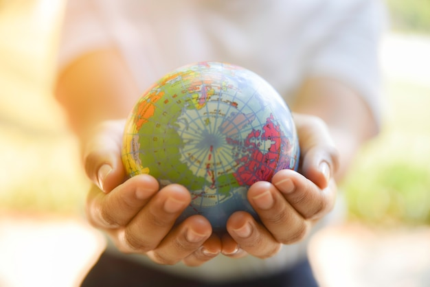 Женщина вручает держать шарик мира на ее руке с естественной зеленой предпосылкой. концепция день окружающей среды мира.
