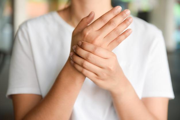 ソファーに座っていたクローズアップの若い女性は彼女の手首を保持します。手のけがと痛みを感じます。