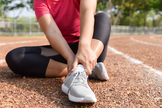 スタジアムトラックの痛みで足首を保持している若い女性。壊れたねじれ関節ランニングスポーツ傷害