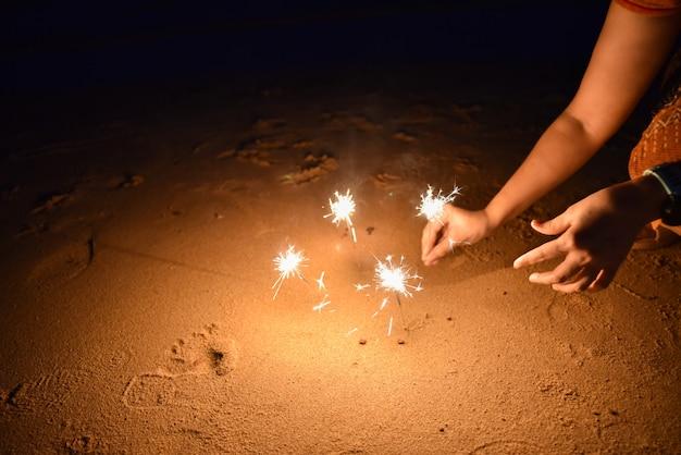 ビーチで花火を持つ女性の手を祝います。