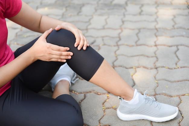 Молодая женщина страдает от травмы колена или коленной чашечки во время тренировки на открытом воздухе на полу.