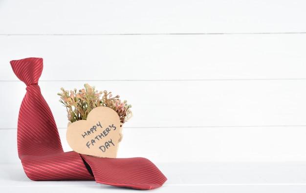 白い木の上の幸せな父の日のテキストと赤いネクタイと茶色のハート紙。