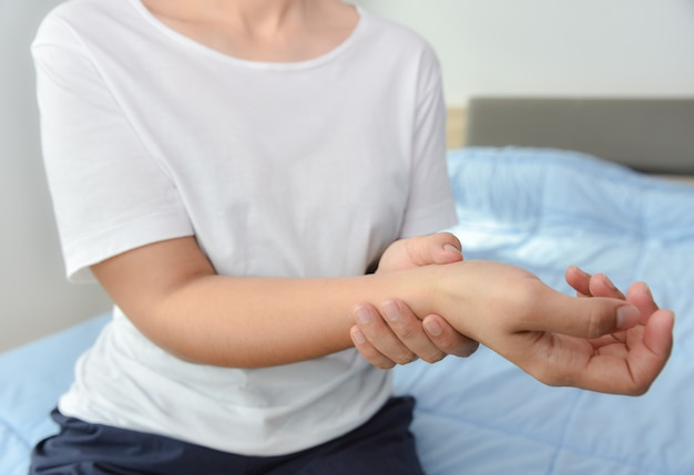 若い女性のクローズアップは、痛みを感じて、彼女の手首の手のけがを保持します。健康管理と医療のコンセプトです。