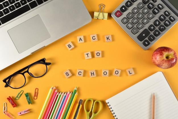 黄色い紙の上の学用品。教育や学校のコンセプトに戻る。
