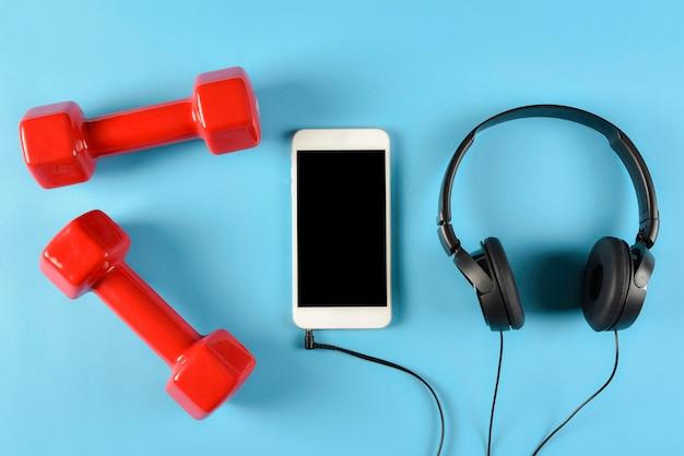 赤いダンベル、黒いヘッドフォンとスマートフォンの平面図です。音楽、スポーツ、フィットネスのコンセプトです。