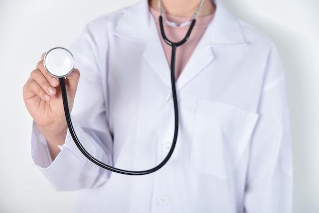 Молодой женский доктор держа стетоскоп в ее руках над белой предпосылкой.