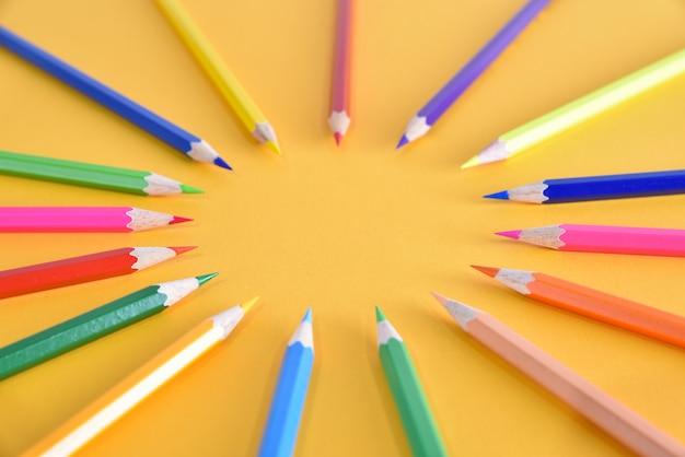Цветные карандаши на желтом фоне. образование, снова в школу концепции, концепция мозгового штурма.