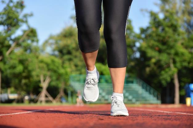 Молодая спортивная женщина бежит по дорожке стадиона по утрам