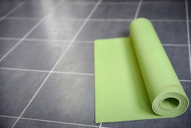 灰色のタイル張りの床に緑のヨガマット