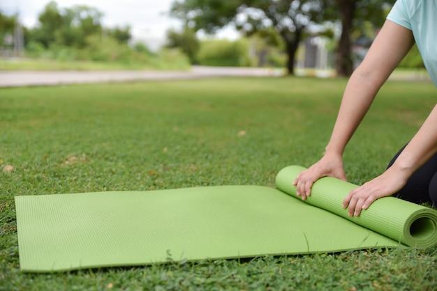 女性の手は、自然な背景を持つ緑の芝生にヨガの仲間をローリングします。