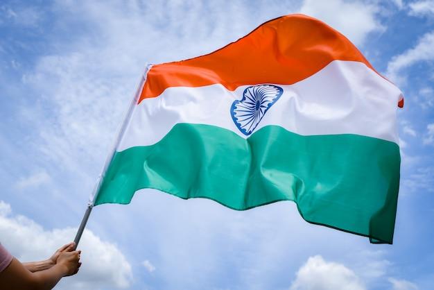 Рука женщины держа флаг индии на предпосылке голубого неба.