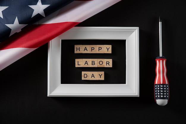 アメリカの国旗と暗い背景に白いフォトフレームで幸せな労働者の日木製テキスト