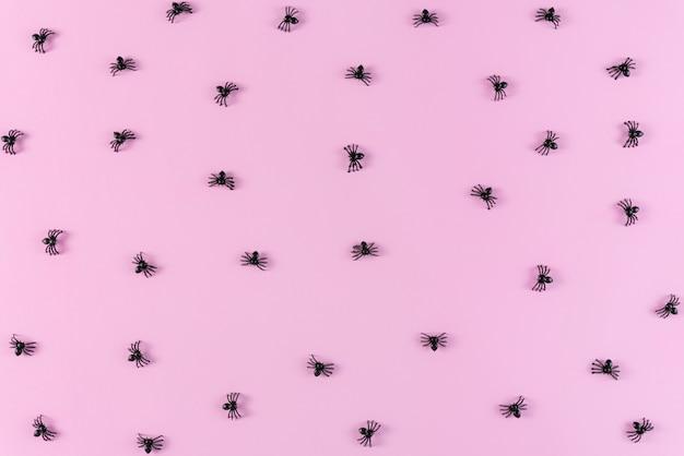 パステルピンクのクモとハロウィーンの休日の背景