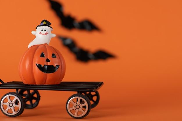 カボチャと白い幽霊とオレンジのコウモリと幸せなハロウィーンの休日の背景