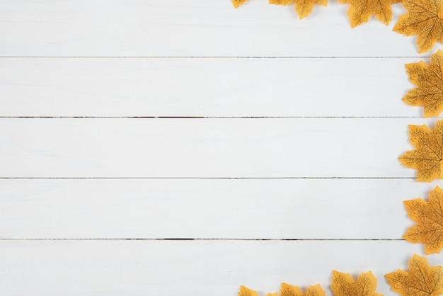 白い木製の背景に黄色のカエデの葉。秋、秋のコンセプト、平面図、コピースペース。