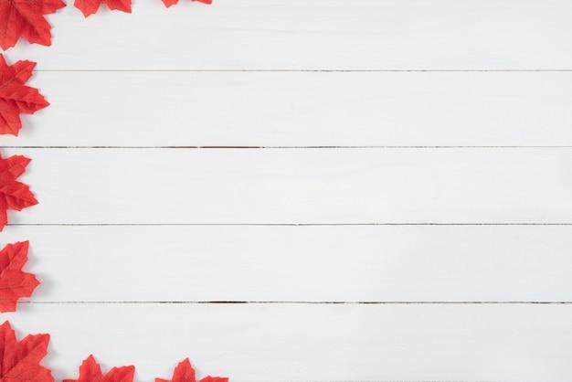 白い木製の背景に赤いカエデの葉。秋、秋のコンセプト、平面図、コピースペース。