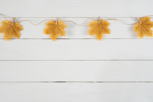 白い木製の背景に黄色のカエデと秋の背景を残します。