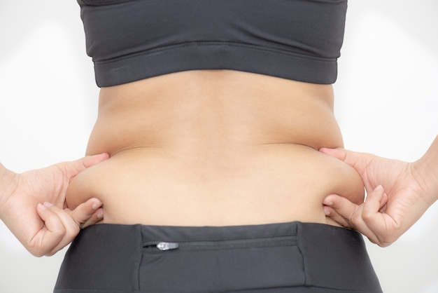 白い背景の上の過度の腹脂肪を持つ太った女性の手。