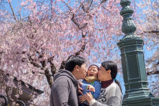 Азиатские мать и отец целуют своего малыша, мальчика, сына в цвету, весенний сад, осмотр достопримечательностей сакуры или вишни
