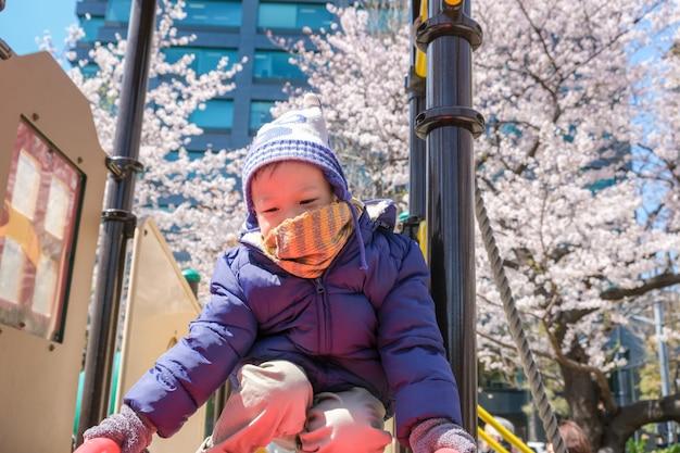 Милый маленький азиатский ребенок мальчика малыша играя на скольжении в спортивной площадке с вишневым цветом сакуры в японии