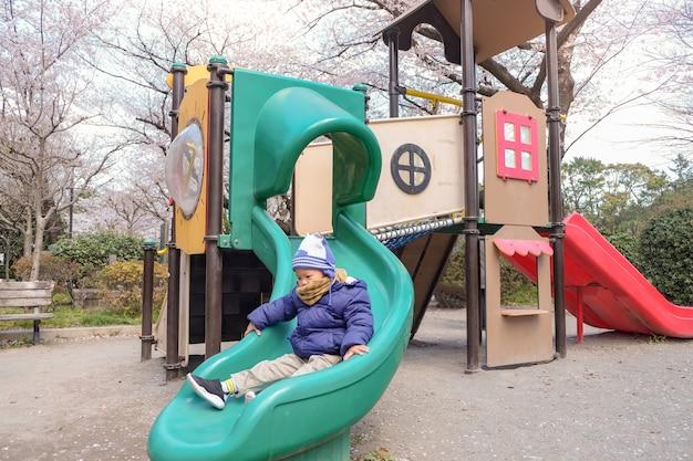 日本のさくら桜と遊び場のスライドで遊ぶかわいい小さなアジア幼児男の子