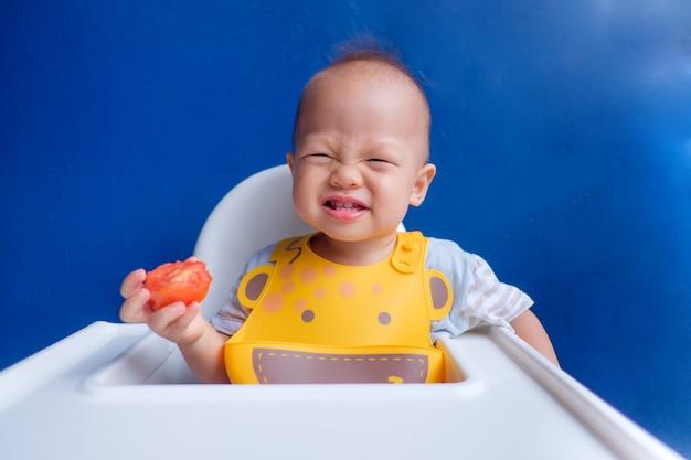 Милый маленький азиатский ребёнок малыша держа и есть красный томат против голубой стены
