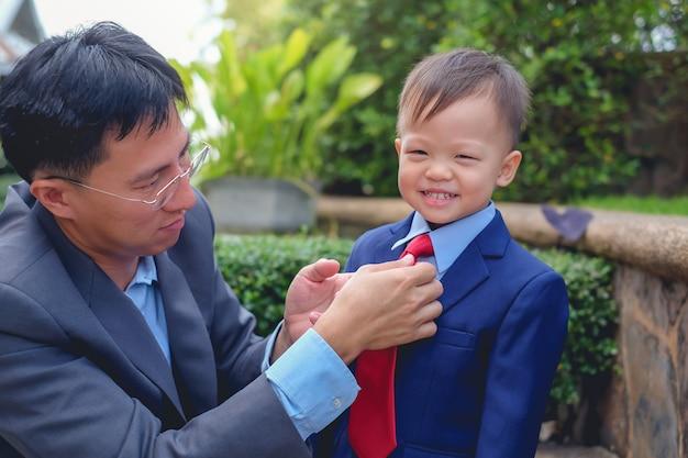 アジアの父と息子がスーツを着て