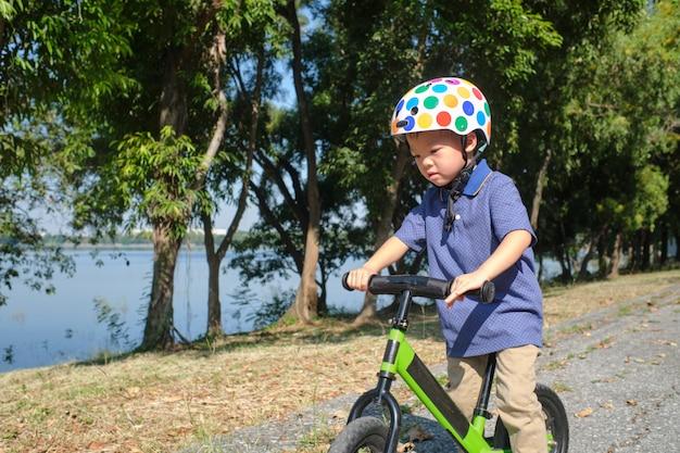 ファーストバランスバイクに乗ることを学ぶ安全ヘルメットを身に着けているアジアの幼児男の子