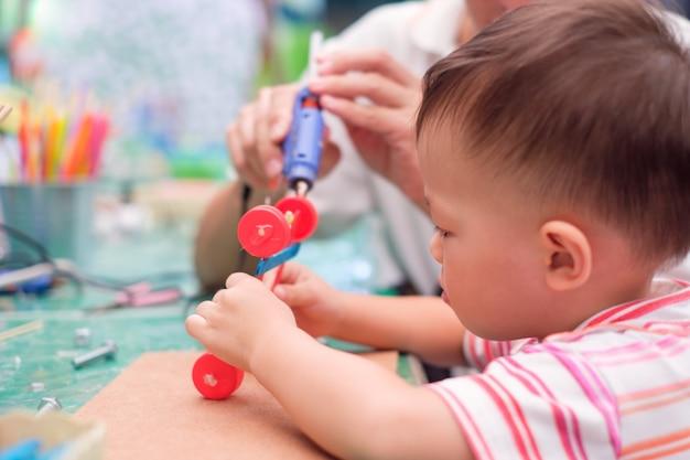 子供を教えるアジアの父親は、リサイクル素材で車のおもちゃを作る。