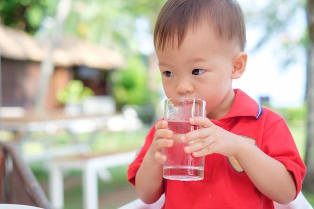 かわいいアジアの幼児男の子の子供がビーチリゾートのレストランで一人で水のガラスを保持&飲むガラスに座って