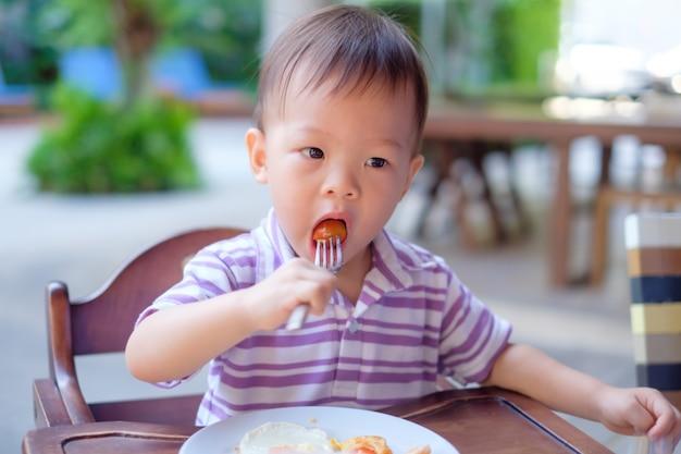 アジアの小さな子供がフォークを使って高い椅子に座っています。