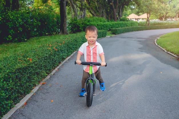 Милый маленький ребенок из азии учится ездить на первом балансирующем велосипеде в солнечный летний день, ребенок играет и катается на велосипеде в парке