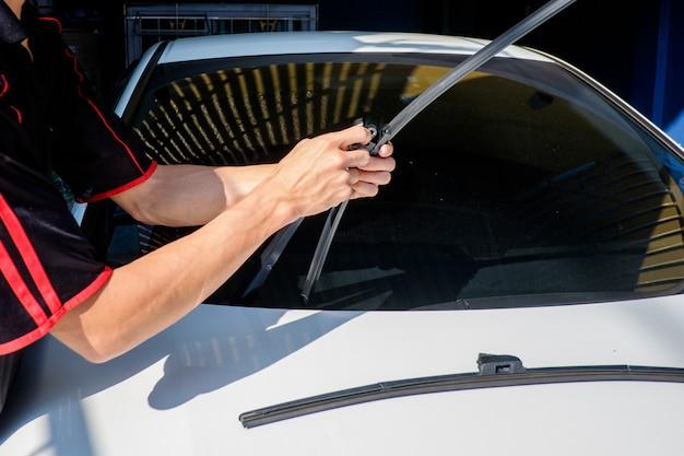 男は車のフロントガラスのワイパーを変更します。