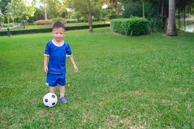 サッカーユニフォームの幼稚園の少年はサッカーをしている